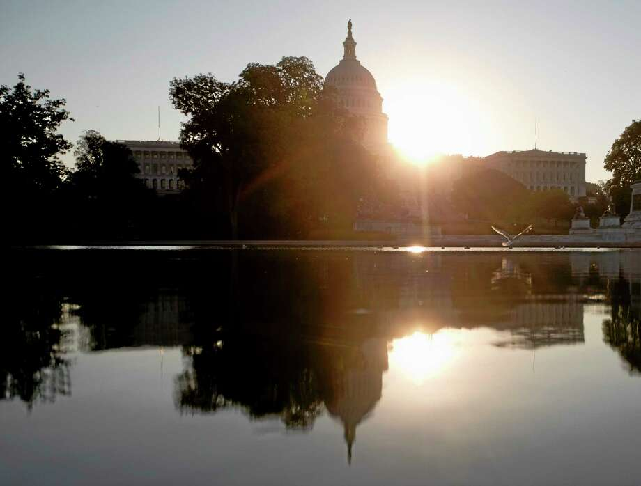 The sun rises behind the Capitol in Washington, Wednesday, Oct. 2, 2013. The political stare-down on Capitol Hill shows no signs of easing, leaving federal government functions _ from informational websites, to national parks, to processing veterans' claims _ in limbo from coast to coast. Lawmakers in both parties ominously suggested the partial shutdown might last for weeks.  (AP Photo/Carolyn Kaster) Photo: AP / AP