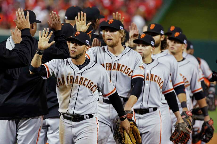 The San Francisco Giants celebrate a 3-2 win over the Nationals in Game 1 of the National League Division Series on Friday in Washington. Photo: Alex Brandon — The Associated Press  / AP
