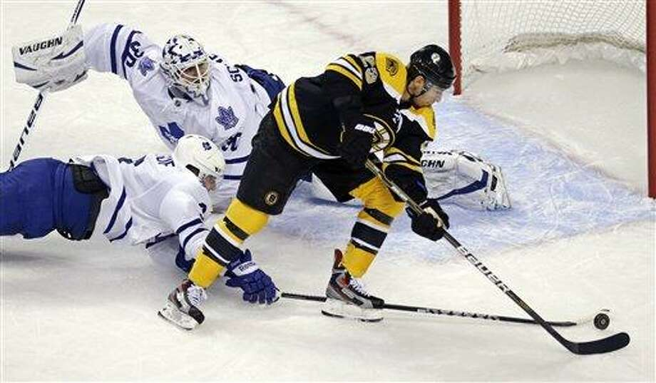 Toronto Maple Leafs defenseman Dion Phaneuf, bottom left, knocks the puck off the stick of Boston Bruins center Chris Kelly (23) as goalie Ben Scrivens (30) looks back during the first period of an NHL hockey game in Boston, Thursday, March 7, 2013. (AP Photo/Charles Krupa) Photo: AP / AP
