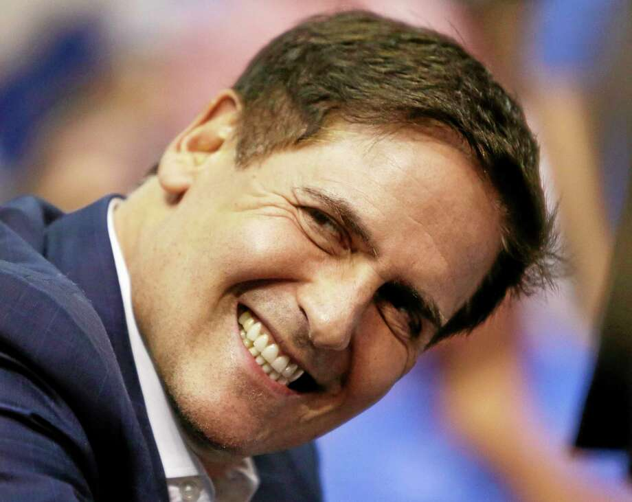 In this March 28 file photo, Dallas Mavericks owner Mark Cuban smiles during an NBA game in Dallas. Opening arguments in the government's insider-trading case against Cuban begin on Tuesday in federal court in Dallas. Photo: Mike Fuentes -- The Associated Press  / FR103746 AP