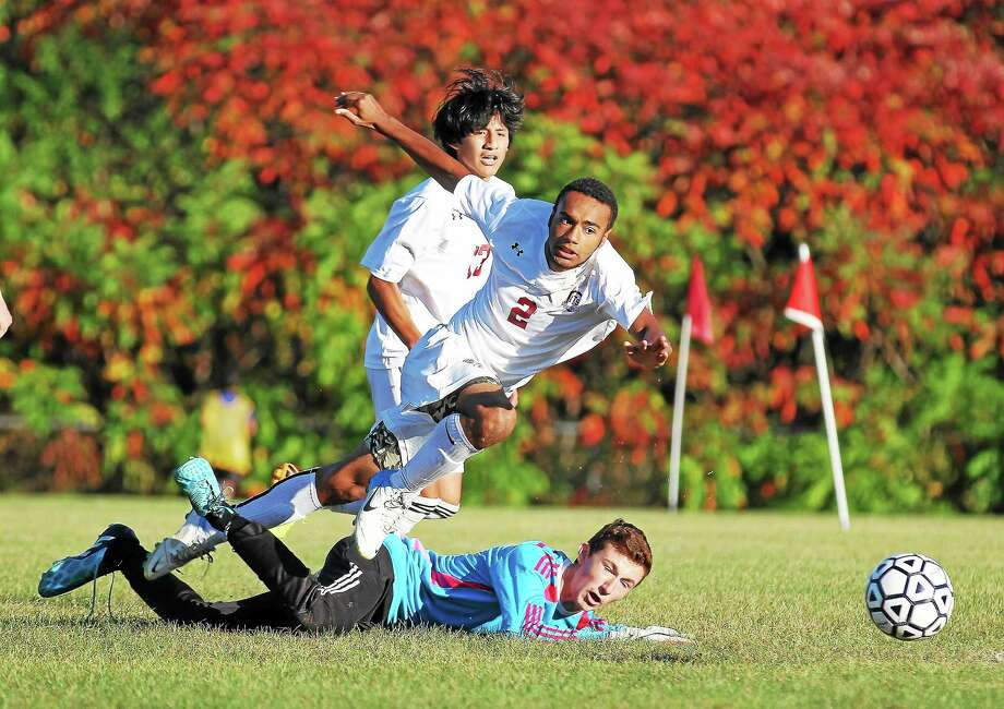 Torrington's Keyon Robinson takes a shot on goal as Oxford's keeper attempts to make a save. Photo: Marianne Killackey - Special To Register Citizen  / 2014