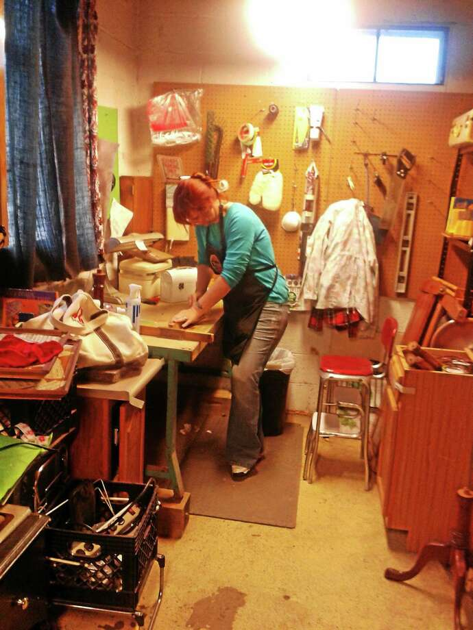 Heather Wing works in the shop at Re-Made in USA, a repurposing business in Harwinton she owns with her husband Don. Photo: Contributed Photo