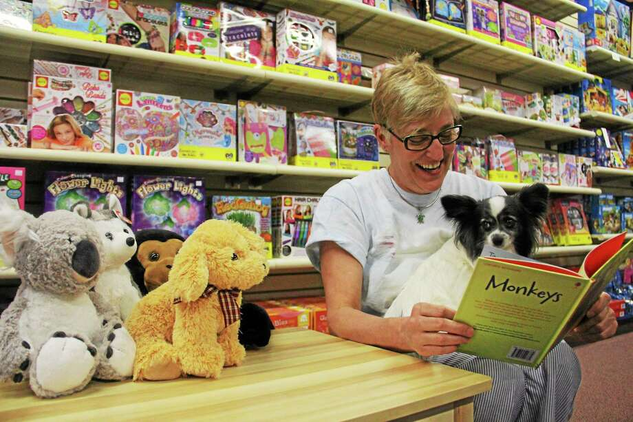 Cheryl Rossi reads to her dog, Tootsie, a 5-year-old Papillion, and few stuffed animals Wednesday inside Toy Jam, located at 52 Main St. in Torrington. Rossi is celebrating 25 years in business on Saturday. Photo: Esteban L. Hernandez — The Register Citizen