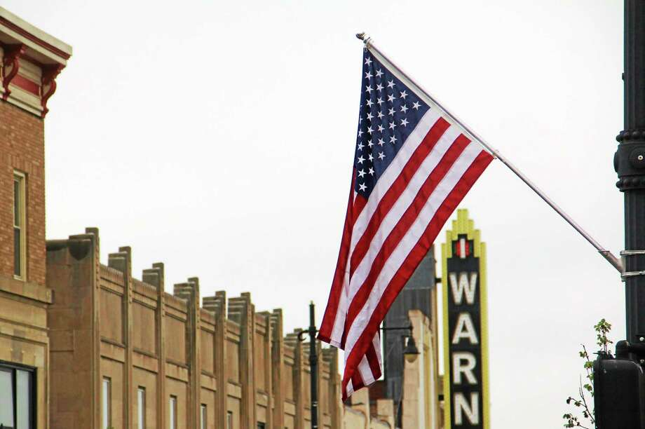 One of the many American flags adorning Main Street that were added by the City rests on a light pole on Thursday in Torrington. Photo: Esteban L. Hernandez — The Register Citizen