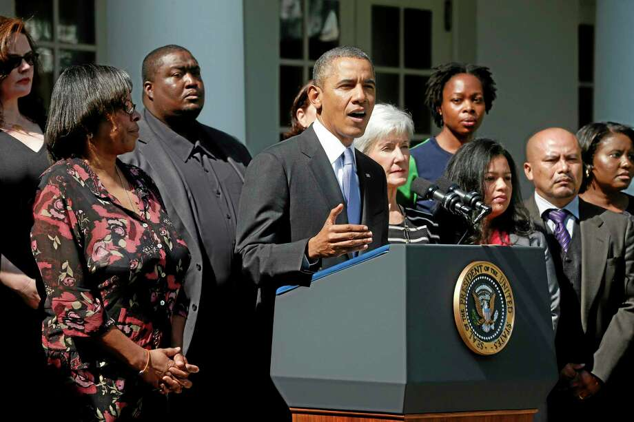 President Barack Obama, accompanied by Health and Human Services Secretary Kathleen Sebelius, and people who support the Affordable Care Act, his signature health care law, speaks in the Rose Garden of the White House in Washington, Tuesday, Oct. 1, 2013. Congress plunged the nation into a partial government shutdown Tuesday as a long-running dispute over President Barack Obama's health care law forced about 800,000 federal workers off the job, suspending all but essential services. (AP Photo/Charles Dharapak) Photo: AP / AP