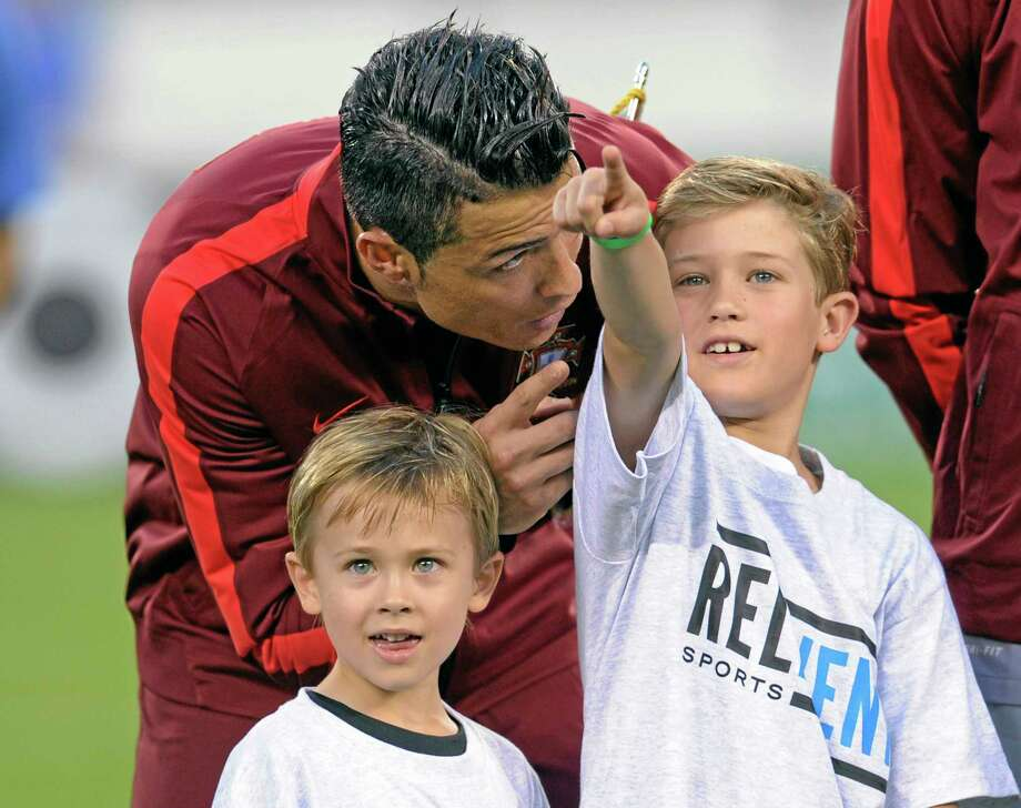 Portugal's Cristiano Ronaldo talks to the children who escorted him out to the pitch before an international friendly against the Republic of Ireland on Tuesday in East Rutherford, New Jersey. Photo: Bill Kostroun — The Associated Press  / FR51951 AP