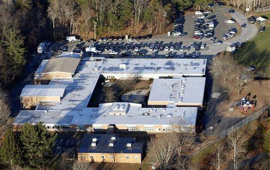 FILE - This Dec. 14, 2012 aerial file photo shows Sandy Hook Elementary School in Newtown, Conn., where a gunman shot 26 people dead. The dispatchers at the Newtown Emergency Communications Center have won praise from officials and colleagues around the country for their role in the response to the shooting. The call center director said the staff has been lifted by the outpouring of support as the dispatchers recover emotionally, along with the community that still peppers them with calls over anything out of the ordinary.  (AP Photo/Julio Cortez, File) Photo: AP / AP