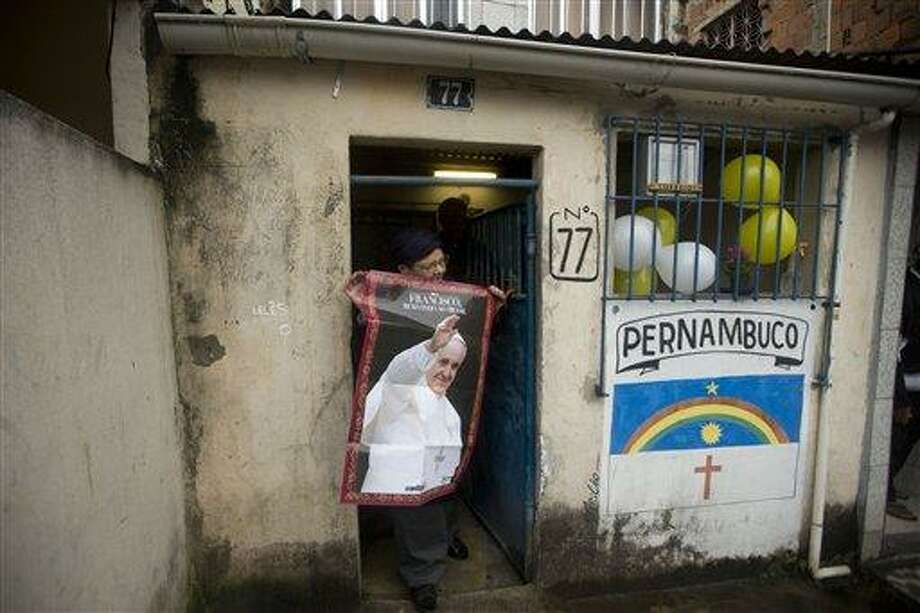"""A woman poses with a poster of Pope Francis outside her home before the Pope's arrival in the Varginha slum in Rio de Janeiro, Brazil, Thursday, July 25, 2013. The writing on the wall reads """"Pernambuco,"""" one of Brazil's states. Pope Francis will bless the Olympic flag, visit this slum and address upward of 1 million young Roman Catholics in Rio de Janeiro's Copacabana beach on Thursday, as Latin America's first pope continued his inaugural international trip as pontiff. (AP Photo/Victor R. Caivano) Photo: AP / AP"""