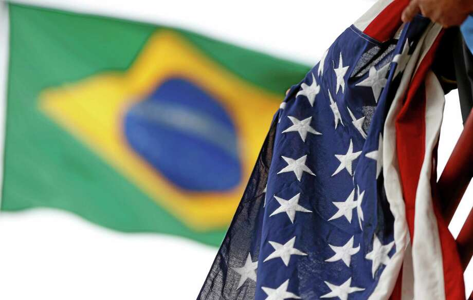 A United States flag owned by Jaime Oquendo, of Houston, Texas, hangs from a railing as a Brazil flag waves in the background as he watches the U.S. men's soccer team during a training session at the Sao Paulo FC training center Wednesday in Sao Paulo, Brazil. Photo: Julio Cortez — The Associated Press  / AP