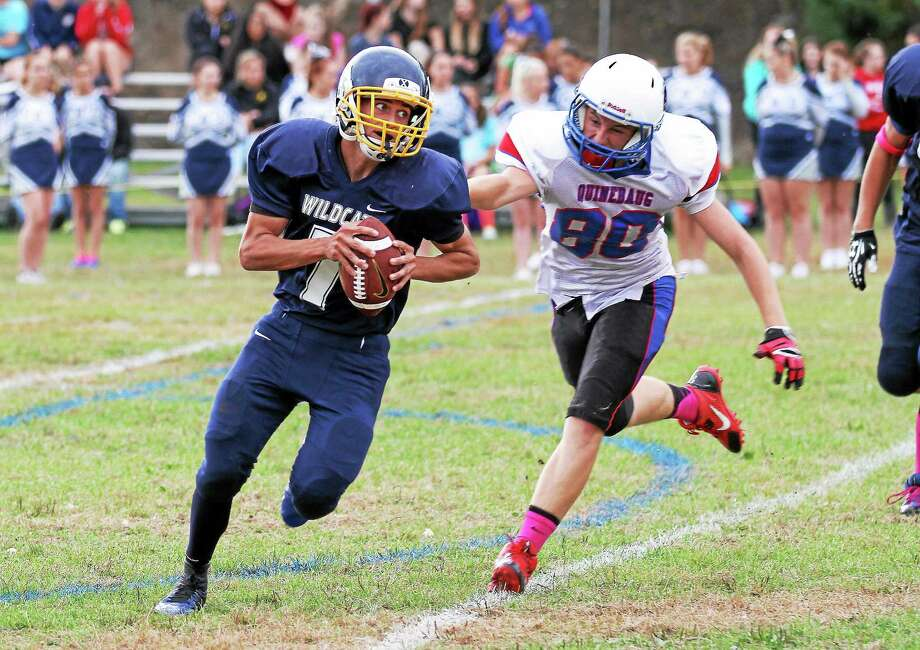 Wolcott Tech quarterback Mickey Ross runs for yardage as a Quinebaug defender gives chase. Photo: Marianne Killackey — Special To Register Citizen  / 2014