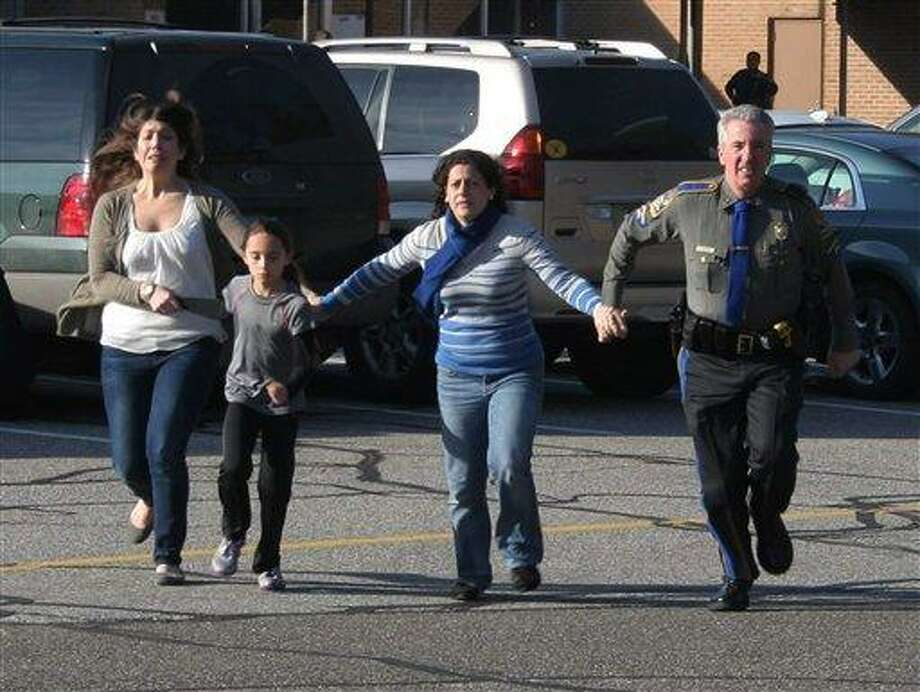 FILE - In this Dec. 14, 2012 file photo provided by the Newtown Bee, a police officer leads two women and a child from Sandy Hook Elementary School in Newtown, Conn., shortly after Adam Lanza opened fire, killing 26 people, including 20 children. While the people of Newtown do their best to cope with loss and preserve the memories of their loved ones, another class of residents is also finding it difficult to move on: the emergency responders who saw firsthand the terrible aftermath of last week's school shooting. (AP Photo/Newtown Bee, Shannon Hicks, File) MANDATORY CREDIT: NEWTOWN BEE, SHANNON HICKS Photo: ASSOCIATED PRESS / AP2012