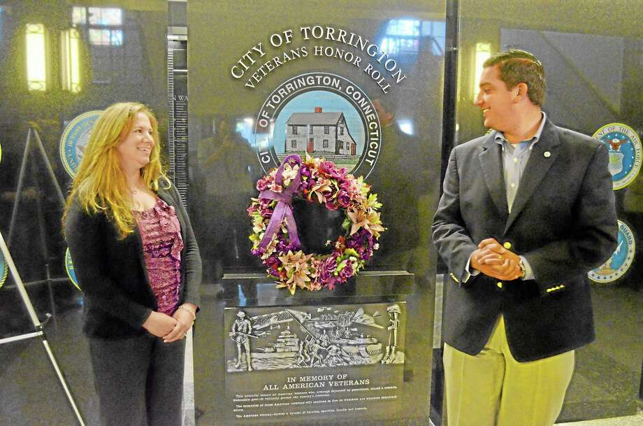 Colleen Sullivan, a community educator at the Susan B. Anthony Project, stands next to a wreath placed by former Torrington Mayor Ryan Bingham, right, during a ceremony that signaled the start of National Domestic Violence Awareness Month at City Hall on Tuesday, Oct. 1. The Susan B. Anthony Project offers support to victims of domestic and sexual abuse and helped organize several events, including this one, to help spread awareness of victims and survivors of domestic violence. Photo: Photos By John Berry — Register Citizen