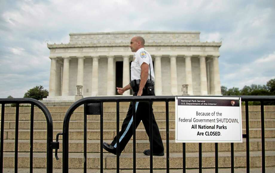"""A US Park Police officer walks behind a barricade with sign reading """"Because of the Federal Government SHUTDOWN All National Parks are Closed"""" in front of the Lincoln Memorial in Washington, Tuesday, Oct. 1, 2013. Congress plunged the nation into a partial government shutdown Tuesday as a long-running dispute over President Barack Obama's health care law stalled a temporary funding bill, forcing about 800,000 federal workers off the job and suspending most non-essential federal programs and services. (AP Photo/Carolyn Kaster) Photo: AP / AP"""
