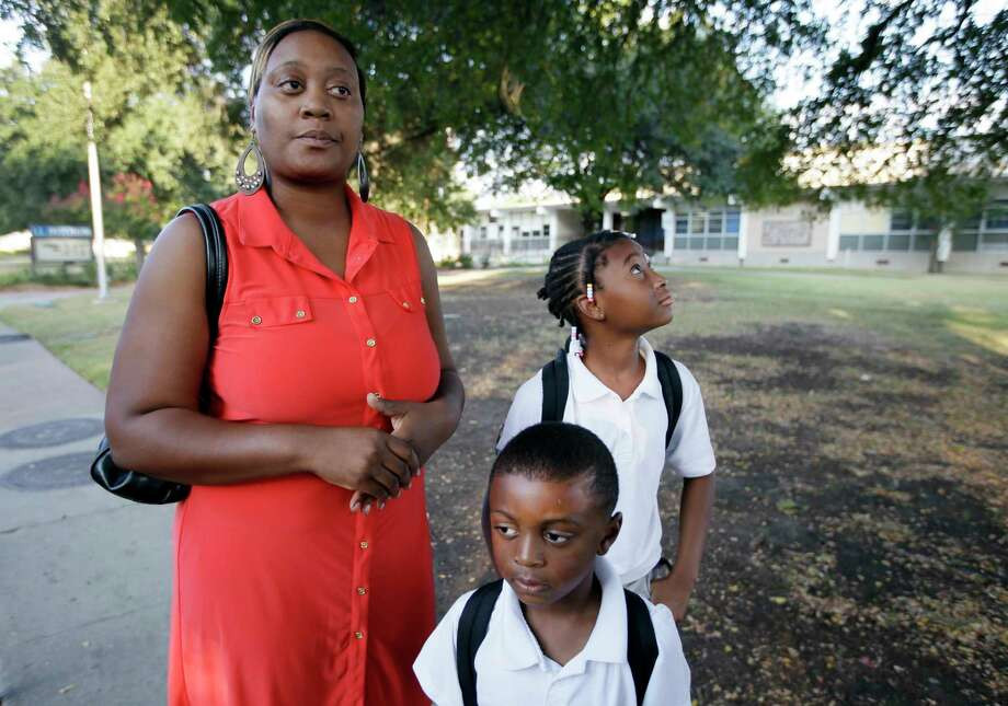 Yasmeen Scott, left, stands by her five-year-old son Bishop, and daughter  Akeelah, 8, before dropping them off at their school, Hotchkiss Elementary, Thursday, Oct. 2, 2014, in Dallas. Hotchkiss has been identified by the Dallas Independent School District as one of the schools where one or more of the students attend that came in contact with the man diagnosed with having the Ebola virus. (AP Photo/Tony Gutierrez) Photo: AP / AP