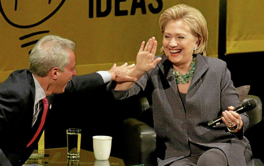 Former Secretary of State Hillary Rodham Clinton laughs with Chicago Mayor Rahm Emanuel after he missed her hand during a high-five attempt, Wednesday, June 11, 2014, in Chicago, during an event promote her new book. (AP Photo/Stacy Thacker) Photo: AP / AP