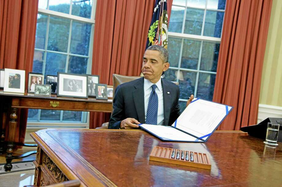 President Barack Obama closes a folder after signing the last of three bills in the Oval Office of the White House on Wednesday, Nov. 27, 2013 in Washington. (AP Photo/ Evan Vucci) Photo: AP / AP