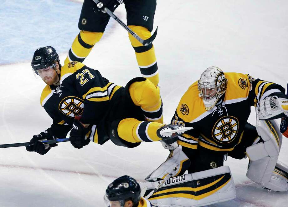Bruins defenseman Dougie Hamilton (27) falls to the ice in front of the crease trying to protect the net with goalie Jeremy Smith (39) in the third period of a preseason game against the New York Islanders on Tuesday in Boston. Photo: Elise Amendola — The Associated Press  / AP