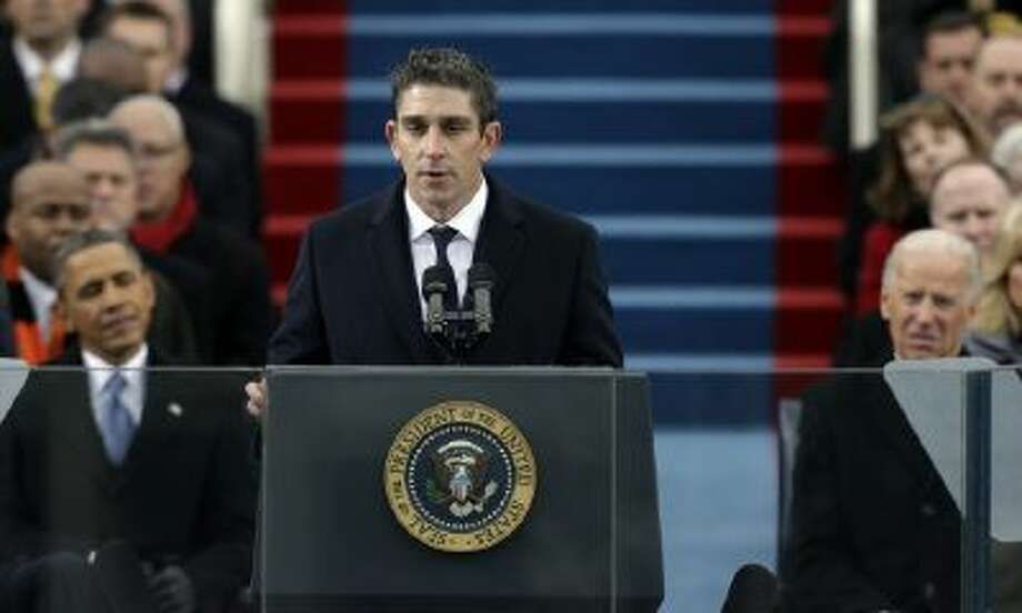 """In this Jan. 21, 2013 file photo, poet Richard Blanco speaks at the U.S. Capitol in Washington during the inauguration for President Barack Obama, left, and Vice President Joe Biden right. Blanco describes writing the inaugural poem in his new book, """"For All of Us, One Today: An Inaugural Poet's Journey."""""""