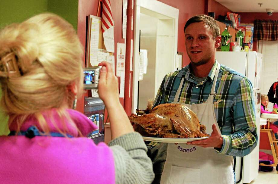 Deirdre Houlihan DiCara, executive director of Friends in Service to Humanity, takes a photo of Earl Gibson, case manager for families and individuals, while he holds a turkey during the FISH Family Thanksgiving Dinner Tuesday in Torrington. FISH helps provide shelter for people without homes and provided a Thanksgiving meal for 35 people who live in its house on South Main Street. Photo: Esteban L. Hernandez — Register Citizen
