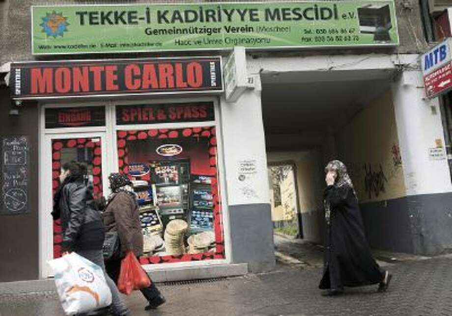 BERLIN, GERMANY - NOVEMBER 02:  Muslim women pass a casino at Karl-Marx-Strasse in Neukoelln district on November 02, 2013 in Berlin, Germany. According to recently published statistics, 7.2 million foreigners were living in Germany by the end of 2012, which is the highest number ever recorded. Of those 80% are from countries in the European Union, while the rest come primarily from Turkey, Russia, the former Soviet states and Arab countries.  (Photo by Carsten Koall/Getty Images) Photo: Getty Images / 2013 Getty Images