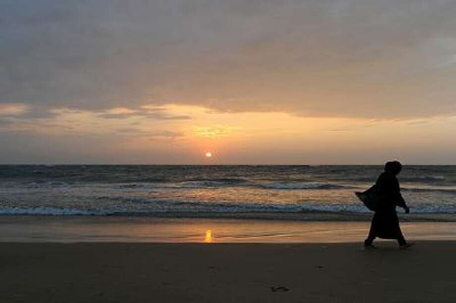 A Sri Lankan beachgoer walks during sunset in Colombo on January 30, 2014. Sri Lanka's youth population aged 10 to 19 make up some 15 percent of its 20 million people. AFP PHOTO/ LAKRUWAN WANNIARACHCHI        (Photo credit should read LAKRUWAN WANNIARACHCHI/AFP/Getty Images) Photo: AFP/Getty Images / 2014 AFP