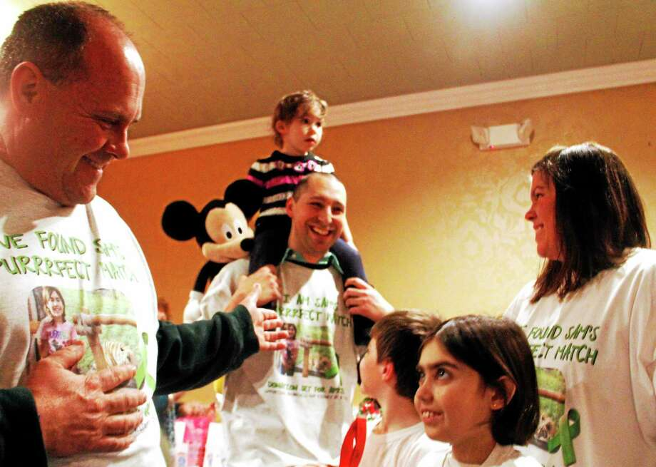 From left: Dan Hall, Raymond Fracasso, Samantha Hall and Heather Ellis smile as Fracasso is announced as the kidney donor for Samantha during a fundraiser at P. Sam's restaurant in Torrington Wednesday. Photo: Esteban L. Hernandez — Register Citizen