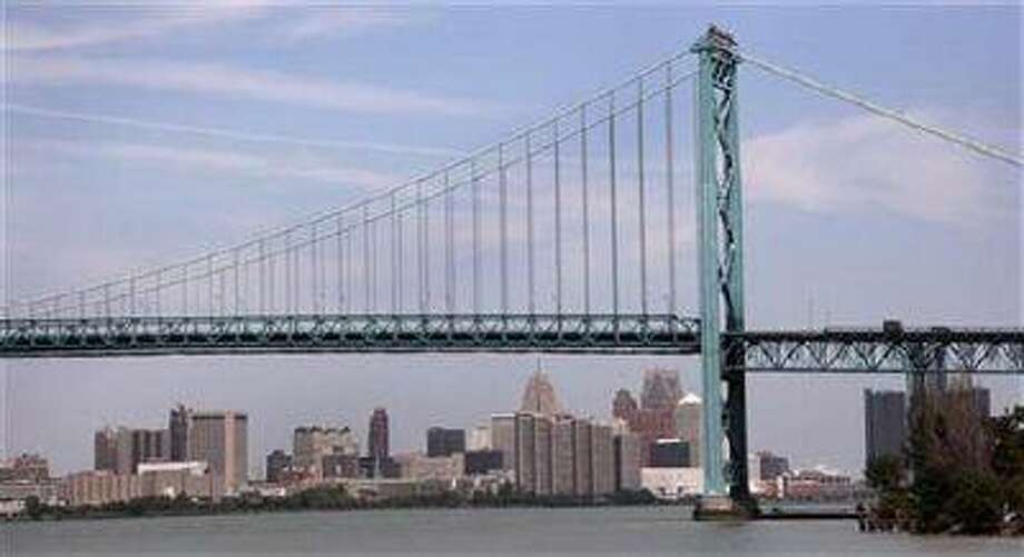 The Detroit city skyline is seen behind the Ambassador Bridge, an international border-crossing linking Windsor, Ontario with Detroit, along the Detroit River in Detroit, Michigan July 21, 2012.