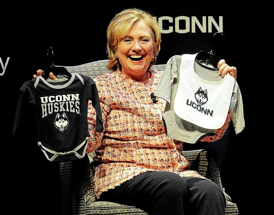 Former Secretary of State Hillary Rodham Clinton holds up UConn Huskies outfits given to her by university president Susan Herbst for Clinton's future grandchild. Photo: AP Photo/Jessica Hill  / FR125654 AP