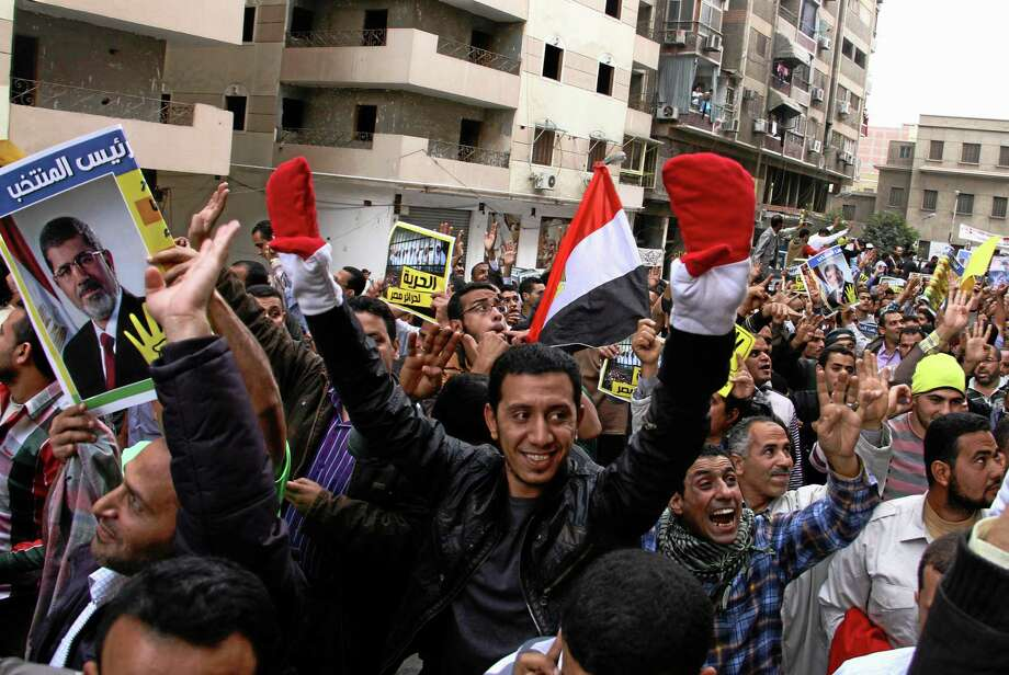 """Supporters of Egypt's ousted President Mohammed Morsi hold a rally against a new law regulating protest in Cairo, Egypt, Friday, Nov. 29, 2013. Hundreds of Islamist demonstrators took to the streets on Friday in cities across Egypt, days after a disputed protest law was adopted and police forcefully broke up unauthorized gatherings. The poster at left shows a picture of the ousted president and the Arabic showing part of a phrase that reads, """"For these reasons, they fight with the elected President."""" (AP Photo/Ahmed Gomaa) Photo: AP / AP"""