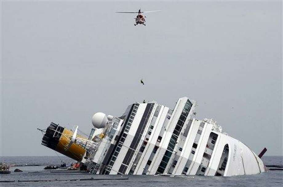 FILE - In this Tuesday, Jan. 31, 2012 file photo, an Italian firefighter is lowered from a helicopter onto the grounded Costa Concordia cruise ship off the Tuscan island of Giglio, Italy. An Italian court on Saturday, July 20, 2013 accepted plea bargains for five Costa Crociere employees in the Costa Concorda shipwreck that killed 32 crew and passengers, convicting all of multiple manslaughter and negligence. (AP Photo/Pier Paolo Cito, File) Photo: AP / AP