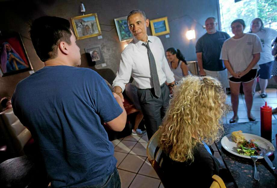 President Barack Obama greets patrons after having lunch during an unannounced visit to FireFlies restaurant in the Del Ray neighborhood of Alexandria, Va.,Tuesday, June 10, 2014. President Barack Obama and Education Secretary Arne Duncan, went on a lunch outing to an Alexandria, Virginia, neighborhood known for its good restaurants. The White House said Obama went to FireFlies Restaurant on Tuesday because the owner wrote him earlier this year and asked him to come try the best burger around. (AP Photo/Pablo Martinez Monsivais) Photo: AP / AP