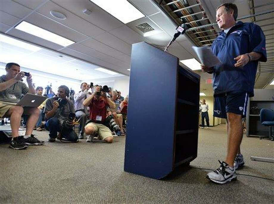 "New England Patriots NFL football head coach Bill Belichick arrives to speak to reporters in Foxborough, Mass., Wednesday, July 24, 2013. Belichick broke his silence four weeks after former Patriots tight end Aaron Hernandez was charged with murder. Belichick says the Patriots will learn from ""this terrible experience,"" and that it's time for New England to ""move forward."" (AP Photo/Josh Reynolds) Photo: AP / FR25426 AP"