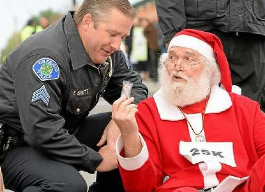 Wal-Mart protester Karl Hilgert hands Ontario police department Sgt. Pat Birkett a candy cane as Hilgert is read his rights before being arrested for failure to disperse.