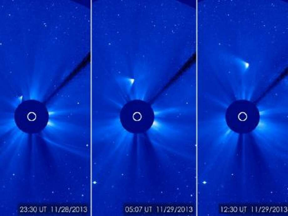 Comet ISON appears as a white smear heading up and away from the sun.
