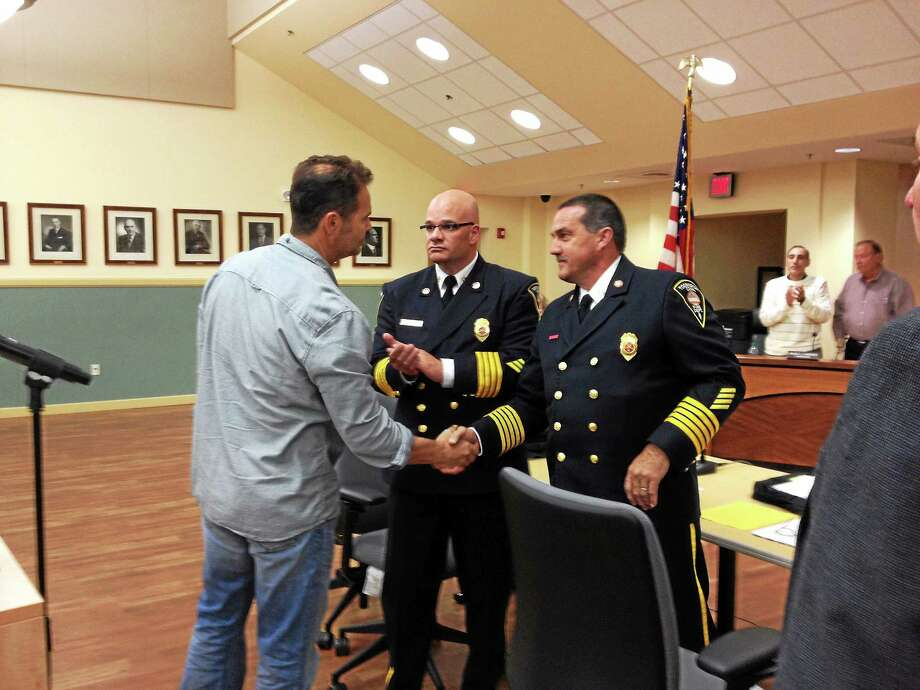Torrington firefighter Mark Garrison shakes hands with Torrington Fire Chief Gary Brunoli after being promoted from firefighter to lieutenant Wednesday. His promotion was one of nine made by the fire and police departments. Photo: Esteban L. Hernandez — The Register Citizen