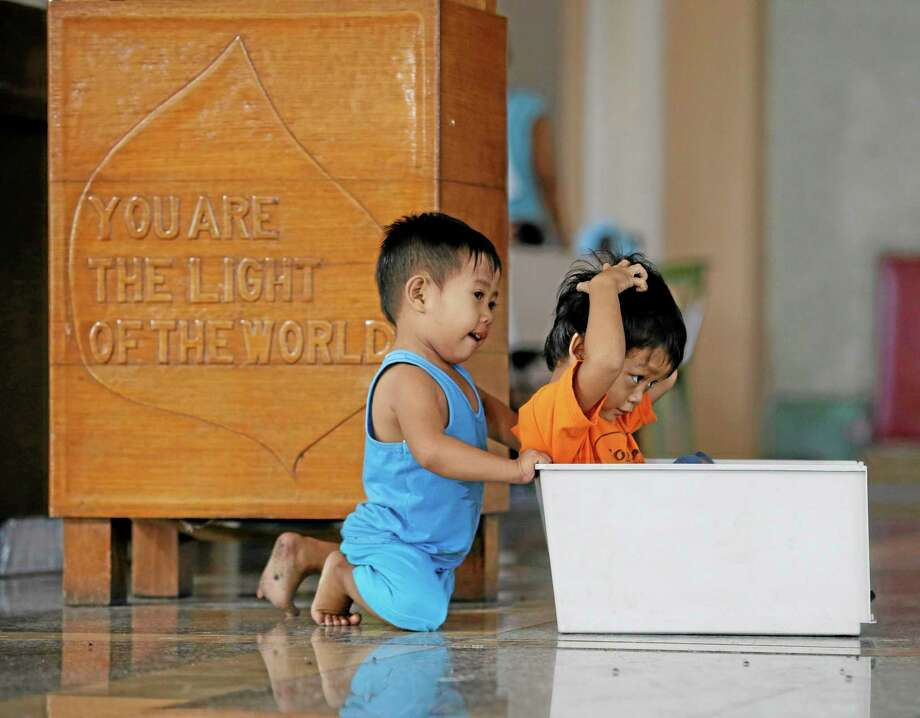 Children play at the altar of the Redemptorist church which is serving as an evacuation center for typhoon survivors Thursday, Nov. 28, 2013,  in Tacloban city, Leyte province in central Philippines. AP Photo/Bullit Marquez Photo: AP / AP