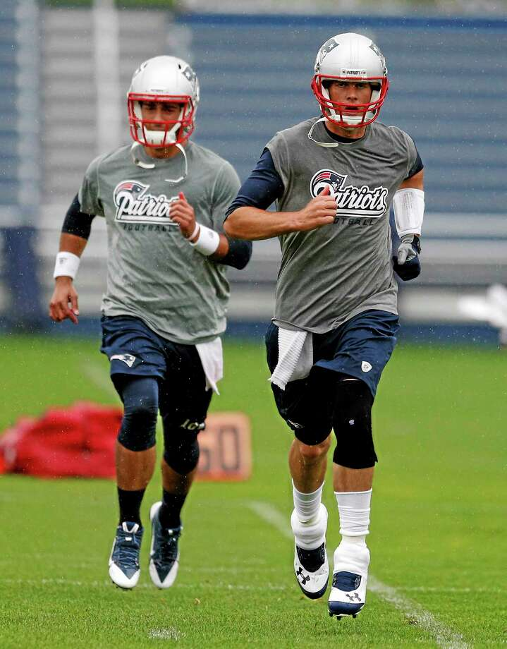 Patriots quarterback Tom Brady, right, and quarterback Jimmy Garoppolo work out during an organized team activity last Thursday. Photo: Michael Dwyer — The Associated Press  / AP