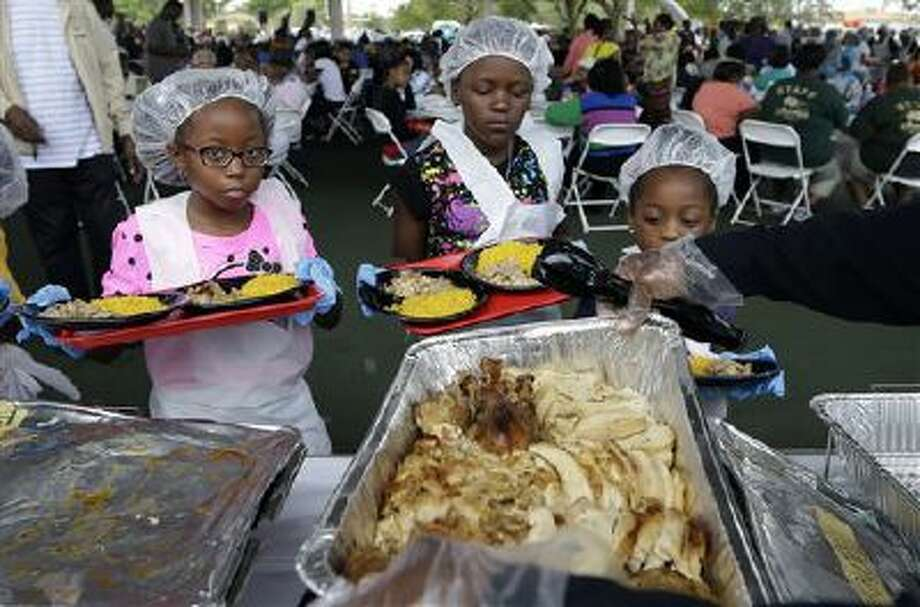 Young helpers get plates loaded Tuesday with turkey before serving them to residents during the annual Thanksgiving luncheon in West Park, Fla. Bags of fresh produce and prepared Thanksgiving meals were handed out. (AP Photo/Lynne Sladky) Photo: AP / AP