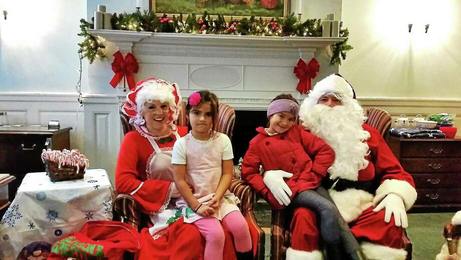 Ailyn, 7, and Cecilia, 5, on Santa Clausí and Mrs. Clausí laps at Union Savings Bank at 13 North St. in Litchfield on Sunday afternoon. Photo: N.F. Ambery — Special To The Register Citizen