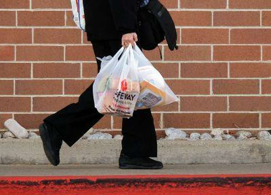 A shopper carries out groceries, Monday November 05, 2012, outside a Safeway in Boulder. The bags that you use could cost you as Boulder will likely begin charging shoppers 10 cents for each paper and plastic bag they use to carry grocer store. City council voted 7-1 Thursday in favor of an ordinance establishing the fee, which would begin in July.RJ Sangosti, The Denver Post Photo: DP / THE DENVER POST