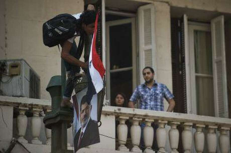 A resident looks on from a balcony as an Egyptian man places the national flag and a poster of ousted president Mohamed Morsi on top of a lamp pole as thousands of Morsi's supporters demonstrate for his reinstatement close to the Egyptian cabinet headquarters earlier this month in Cairo. AFP/Getty Images/Gianluigi Guercia) Photo: AFP/Getty Images / 2013 AFP