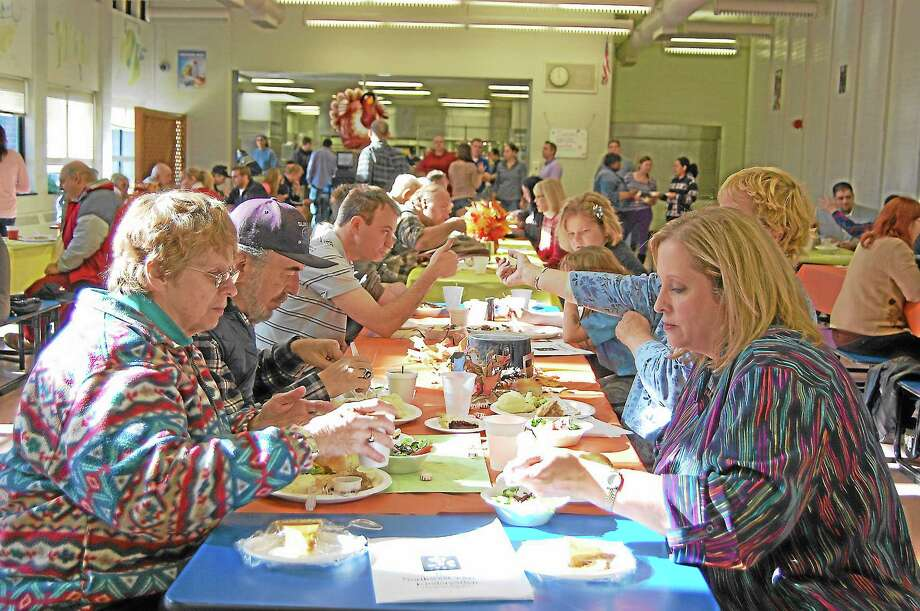 Visitors enjoy a Thanksgiving dinner put on by volunteers at Oliver Technical Wolcott High School in Torrington on Nov. 28. Photo: Mercy Quaye—Register Citizen