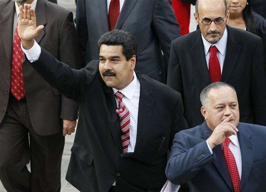 """Venezuela's Vice President Nicolas Maduro, left, and Diosdado Cabello, president of Venezuela's National Assembly, gesture to supporters as they arrive to the National Assembly for the state-of-the-nation address in Caracas, Venezuela, Thursday, Feb. 28, 2013.  Maduro, Chavez's self-appointed successor, said on television that his boss """"is battling there for his health, for his life, and we're accompanying him."""" (AP Photo/Ariana Cubillos) Photo: AP / AP"""