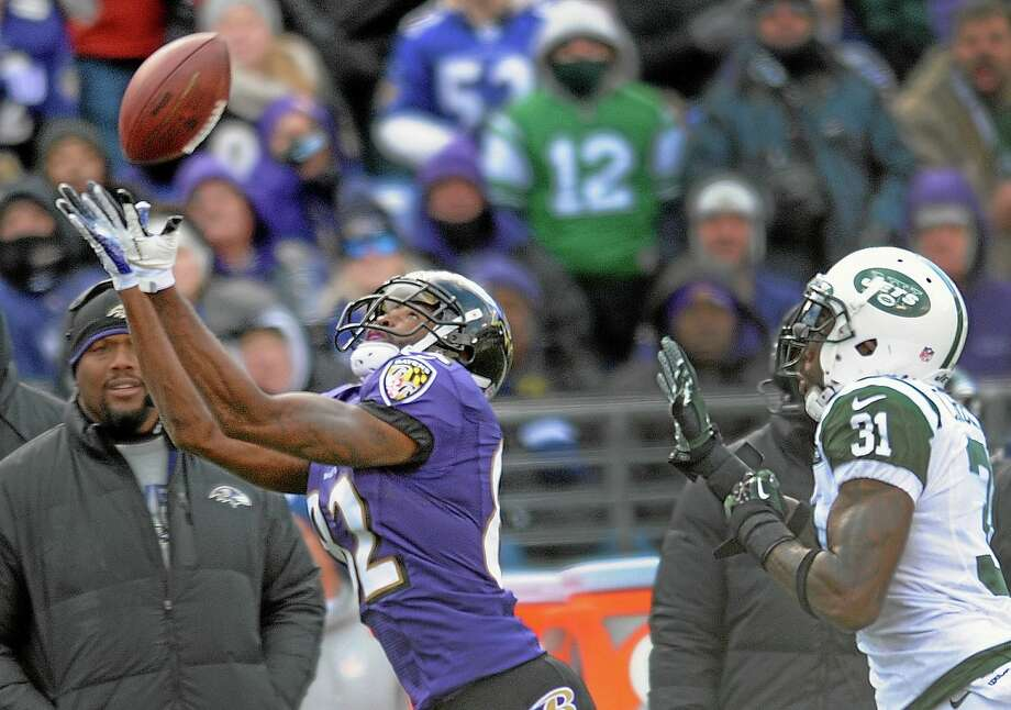 Ravens wide receiver Torrey Smith pulls in a pass under pressure from New York Jets cornerback Antonio Cromartie, right, during Sunday's game in Baltimore. Photo: Gail Burton — The Associated Press  / FR4095 AP