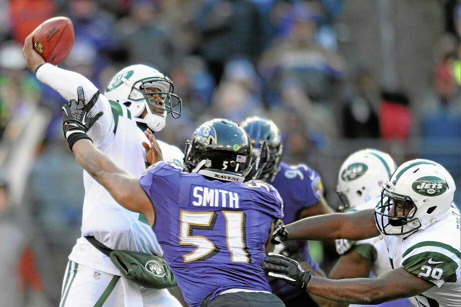 New York Jets quarterback Geno Smith, left, passes the ball under pressure from Ravens inside linebacker Daryl Smith (51) during Sunday's game in Baltimore. Photo: Gail Burton — The Associated Press  / FR4095 AP