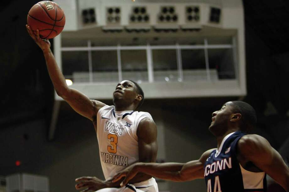 West Virginia guard Juwan Staten, left, goes to the basket against UConn guard Rodney Purvis during the title game of the Puerto Rico Tip-Off tournament last Sunday in San Juan. Photo: Ricardo Arduengo — The Associated Press  / AP