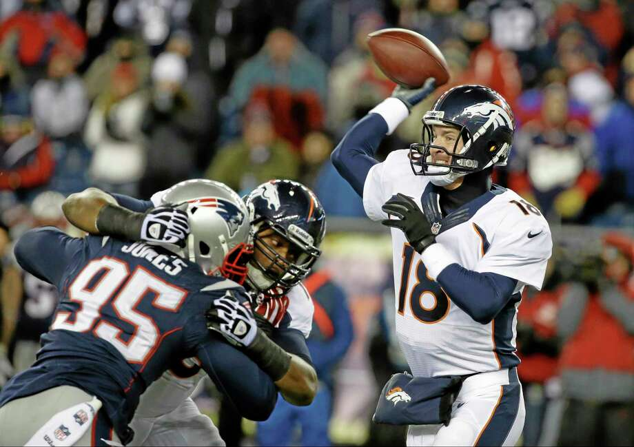 Denver Broncos quarterback Peyton Manning passes against New England Patriots defensive end Chandler Jones (95) in Sunday's game in Foxborough, Mass. Photo: Stephan Savoia — The Associated Press  / AP