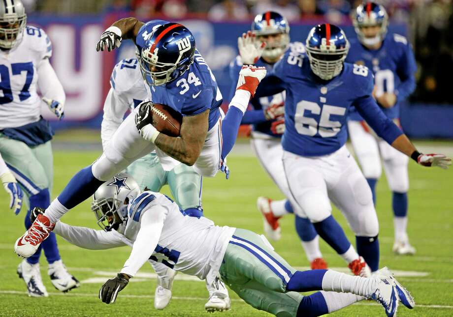 New York Giants running back Brandon Jacobs (34) leaps over Dallas Cowboys strong safety J.J. Wilcox during Sunday's game in East Rutherford, N.J. Photo: Seth Wenig — The Associated Press  / AP