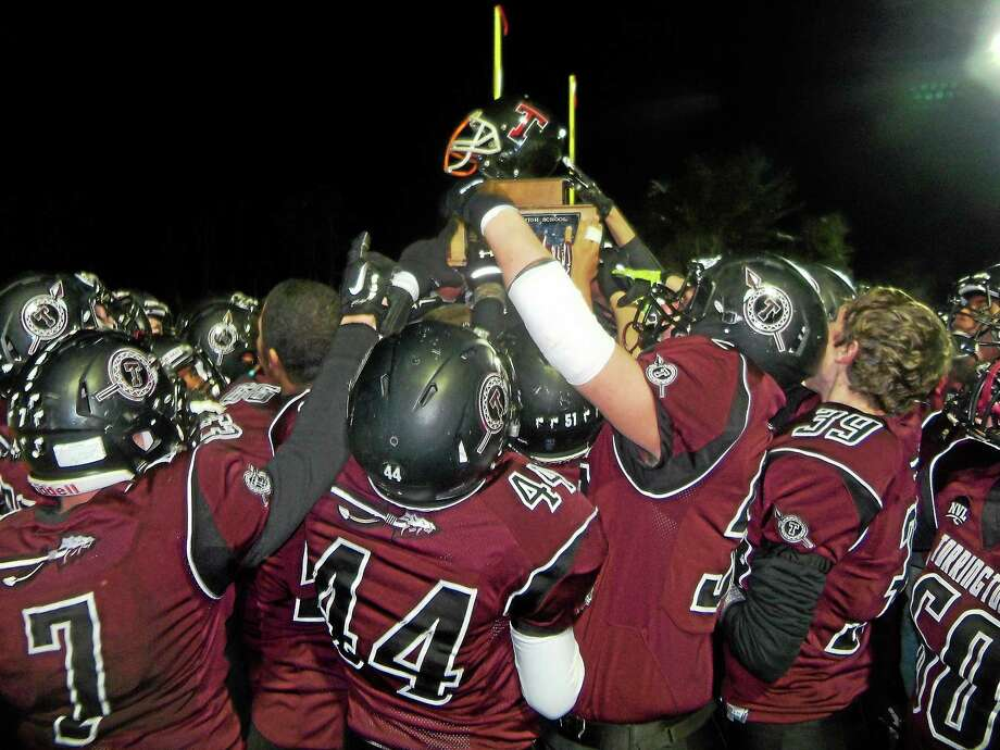 Torrington celebrates by raising 'The Helmet' after defeating Watertown 55-43 Saturday. Photo: Peter Wallace — Register Citizen