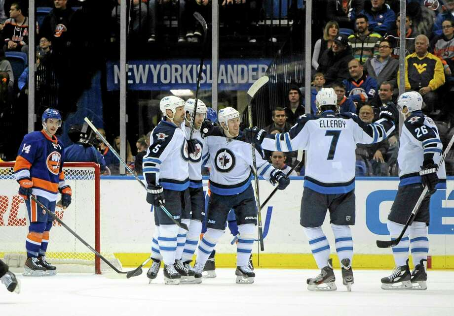 The Islanders' Thomas Hickey (14) watches the Winnipeg Jets' Andrew Ladd (16), second from left, celebrate his goal with teammates in the second period of Wednesday's game in Uniondale, N.Y. Photo: Kathy Kmonicek — The Associated Press  / FR170189 AP
